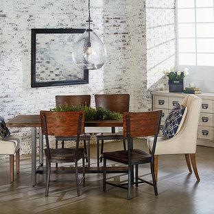 Esempio di una sala da pranzo industriale con pareti bianche, pavimento in cemento e nessun camino