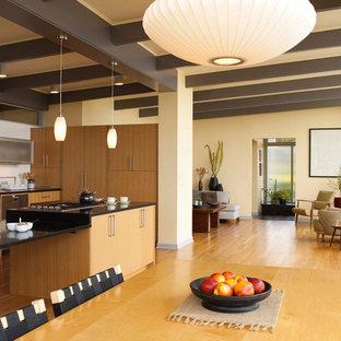 Foto di una grande sala da pranzo aperta verso il soggiorno moderna con pareti beige, pavimento in legno massello medio e nessun camino