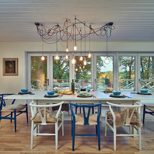 Inspiration for a bohemian open plan dining room in London with white walls, medium hardwood flooring and brown floors.