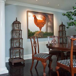 Foto di una grande sala da pranzo aperta verso il soggiorno boho chic con pareti grigie, parquet scuro, camino classico e cornice del camino in legno
