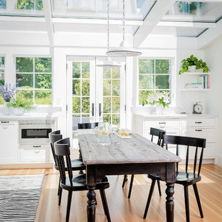 Kitchen/dining room combo - beach style medium tone wood floor and beige floor kitchen/dining room combo idea in Boston with white walls