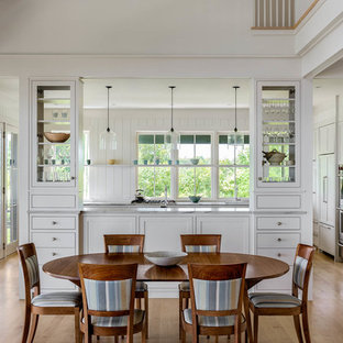 Medium sized beach style kitchen/dining room in Portland Maine with white walls and light hardwood flooring.