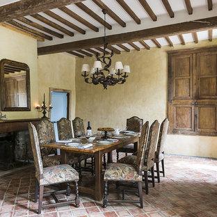 Cette photo montre une grand salle à manger chic fermée avec un mur beige, un sol en carreau de terre cuite, une cheminée standard et un manteau de cheminée en pierre.