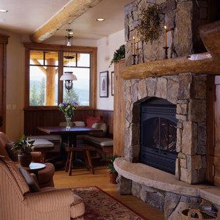 Foto de comedor rústico, pequeño, abierto, con paredes beige, suelo de madera clara, chimenea tradicional, marco de chimenea de piedra y suelo marrón