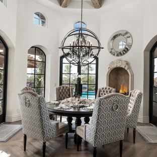 Esempio di un'ampia sala da pranzo moderna chiusa con pareti bianche, pavimento in legno massello medio, camino sospeso, cornice del camino in pietra e pavimento marrone