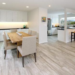 Пример оригинального дизайна: большая кухня-столовая в стиле модернизм с белыми стенами, полом из керамогранита, подвесным камином, фасадом камина из плитки и серым полом