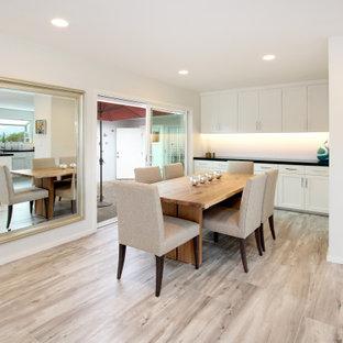 他の地域の広いモダンスタイルのおしゃれなダイニングキッチン (白い壁、磁器タイルの床、吊り下げ式暖炉、タイルの暖炉まわり、グレーの床) の写真