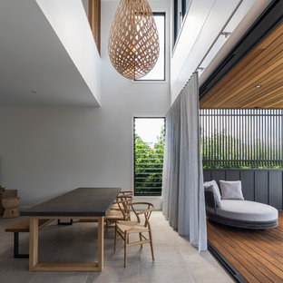 Mid-sized contemporary dining room in Brisbane with white walls, concrete floors and beige floor.