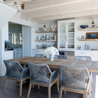 Esempio di una piccola sala da pranzo aperta verso la cucina al mare con pareti bianche, pavimento in legno massello medio, camino classico, cornice del camino in mattoni e pavimento grigio