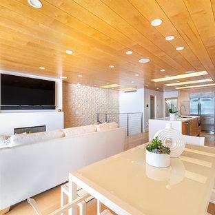 Ispirazione per un'ampia sala da pranzo aperta verso il soggiorno design con pareti bianche, parquet chiaro, camino classico, cornice del camino in pietra e pavimento giallo