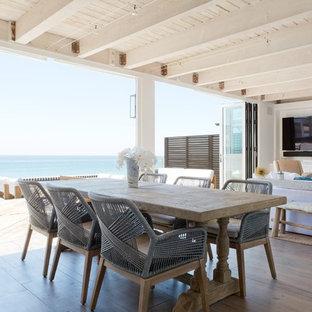 Diseño de comedor costero, de tamaño medio, abierto, con paredes blancas y suelo de madera en tonos medios