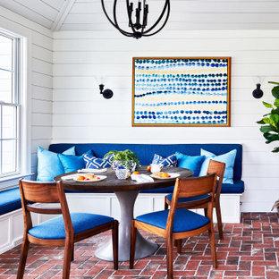 Exemple d'une salle à manger bord de mer avec une banquette d'angle, un mur blanc, un sol en brique, un sol rouge, un plafond en lambris de bois, un plafond voûté et du lambris de bois.