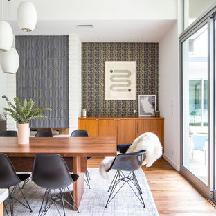 Photo of a midcentury open plan dining in Los Angeles with white walls, medium hardwood floors and brown floor.