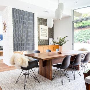 Diseño de comedor retro, abierto, con paredes blancas, suelo de madera en tonos medios, chimenea de doble cara, marco de chimenea de baldosas y/o azulejos y suelo marrón