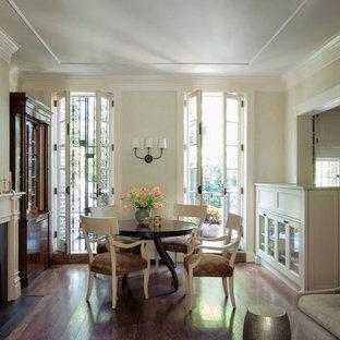 Diseño de comedor clásico, pequeño, abierto, con paredes blancas, suelo de madera oscura, chimenea tradicional y marco de chimenea de metal