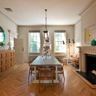На фото: большая столовая в стиле модернизм с белыми стенами, паркетным полом среднего тона, стандартным камином и фасадом камина из камня с