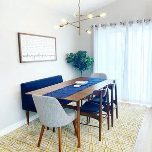 Immagine di una sala da pranzo aperta verso la cucina moderna di medie dimensioni con pareti grigie, pavimento in laminato e pavimento marrone