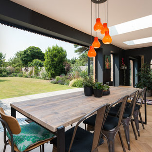 Photo of a medium sized eclectic dining room in Kent with black walls, light hardwood flooring and beige floors.