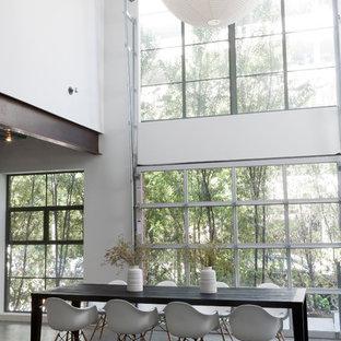 Ispirazione per una sala da pranzo industriale con pavimento in cemento