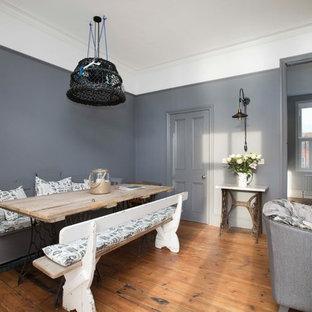 ケントの大きいシャビーシック調のおしゃれなLDK (グレーの壁、無垢フローリング、茶色い床、標準型暖炉、金属の暖炉まわり) の写真