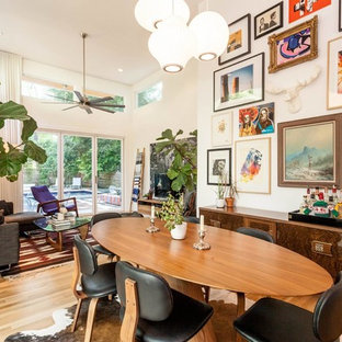Example of a mid-sized eclectic light wood floor and brown floor great room design in Austin with white walls