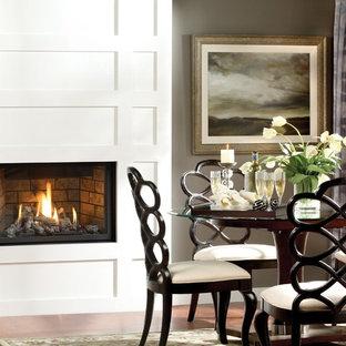 Foto de comedor minimalista con paredes grises, marco de chimenea de madera y chimenea lineal