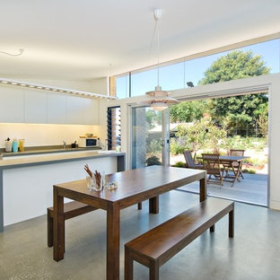Design Ideas For A Contemporary Kitchen/dining Combo In Melbourne With  White Walls And Concrete