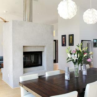 Foto de comedor minimalista, de tamaño medio, abierto, con paredes blancas, suelo de bambú, chimenea de doble cara y marco de chimenea de hormigón