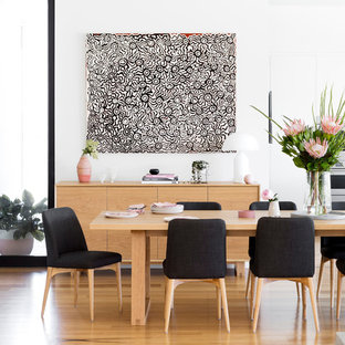 This is an example of a contemporary kitchen/dining combo in Melbourne with white walls, medium hardwood floors and brown floor.