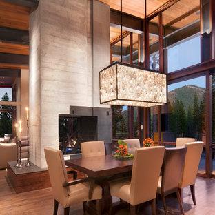 Esempio di una sala da pranzo aperta verso il soggiorno rustica con cornice del camino in cemento e camino bifacciale
