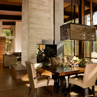 Foto di una grande sala da pranzo aperta verso il soggiorno in montagna con pareti beige, pavimento in legno massello medio, camino bifacciale e cornice del camino in cemento