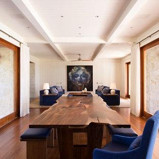 Cette photo montre une grande salle à manger ouverte sur le salon exotique avec un mur blanc, un sol en bois brun, aucune cheminée et un sol marron.