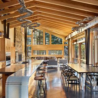 Immagine di una grande sala da pranzo aperta verso il soggiorno minimal con pavimento in cemento
