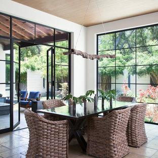 Ispirazione per una sala da pranzo mediterranea con pareti bianche e pavimento in travertino