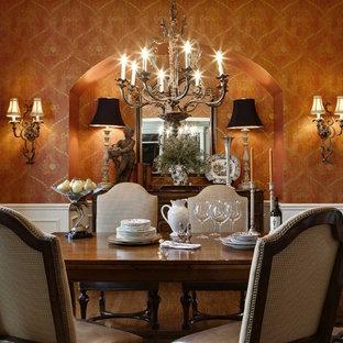 Imagen de comedor clásico, cerrado, con parades naranjas y suelo de madera en tonos medios