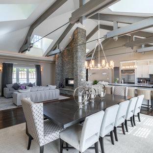 Réalisation d'une grand salle à manger ouverte sur le salon tradition avec un mur beige, un sol en bois foncé, une cheminée double-face et un manteau de cheminée en brique.