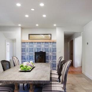 Idée de décoration pour une salle à manger ouverte sur la cuisine nordique de taille moyenne avec un mur blanc, un sol en calcaire, un poêle à bois et un manteau de cheminée en carrelage.