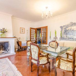 Ispirazione per una sala da pranzo aperta verso il soggiorno mediterranea con pareti bianche, pavimento in terracotta, camino classico e pavimento rosso