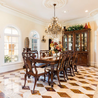 Example of a large tuscan marble floor and multicolored floor enclosed dining room design in Orlando with beige walls and no fireplace