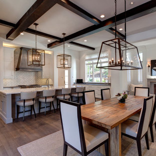 Example of a large tuscan dark wood floor and white floor great room design in Dallas with white walls, a standard fireplace and a concrete fireplace