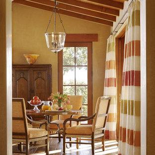 Aménagement d'une salle à manger méditerranéenne avec un mur beige et un sol en bois brun.