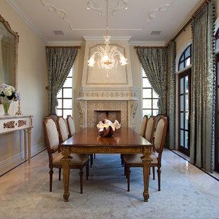 Immagine di una grande sala da pranzo tradizionale chiusa con pareti beige, pavimento in marmo, camino classico, cornice del camino in legno e pavimento beige