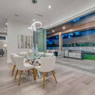 Immagine di una sala da pranzo minimal di medie dimensioni con pareti bianche, pavimento in laminato, camino classico, cornice del camino in cemento e pavimento grigio