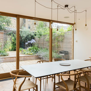 Contemporary kitchen/dining room in London with white walls, medium hardwood flooring and brown floors.