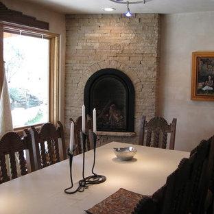 Réalisation d'une salle à manger ouverte sur la cuisine sud-ouest américain avec un mur beige, une cheminée d'angle et un manteau de cheminée en pierre.