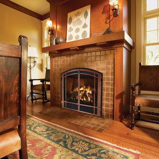 Modelo de comedor de estilo americano, grande, cerrado, con paredes amarillas, suelo de madera en tonos medios, chimenea tradicional, marco de chimenea de baldosas y/o azulejos y suelo marrón