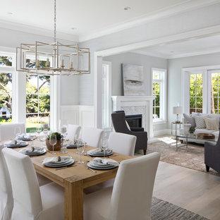 Ejemplo de comedor clásico renovado, grande, cerrado, con paredes grises, suelo de madera clara, suelo beige, chimenea tradicional y marco de chimenea de piedra