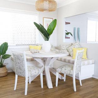 Cette photo montre une salle à manger ouverte sur la cuisine bord de mer de taille moyenne avec un mur gris et un sol en vinyl.