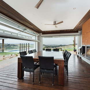 Country dining room in Geelong with dark hardwood floors, a ribbon fireplace, a metal fireplace surround and brown floor.