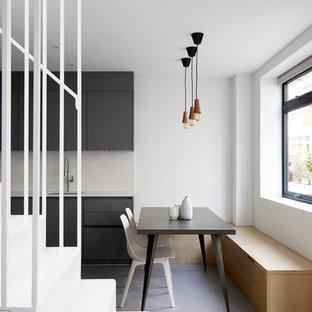 Ejemplo de comedor de cocina actual, pequeño, sin chimenea, con suelo gris, paredes blancas y suelo de cemento